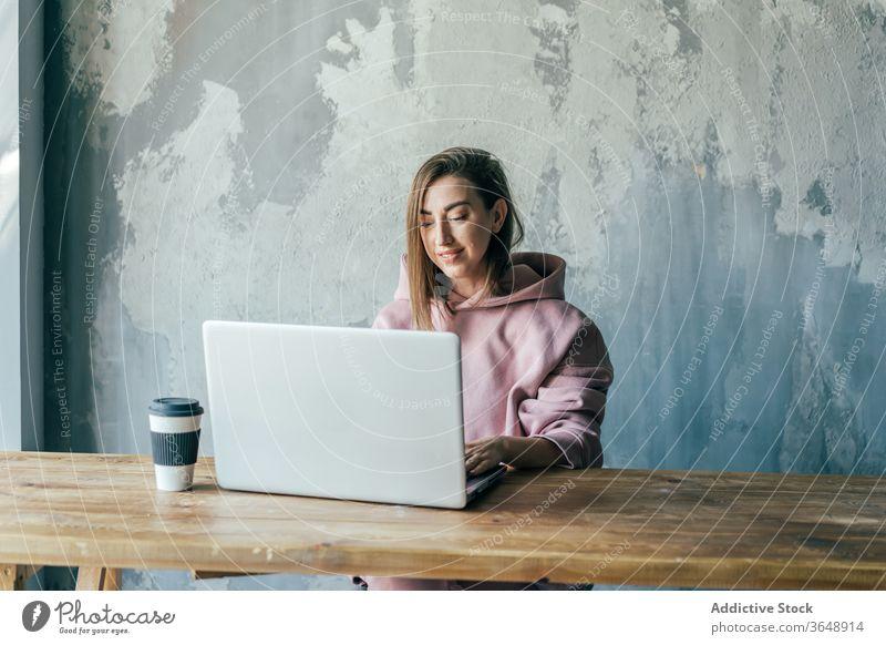Weibliche Freiberuflerin tippt auf Laptop in der Nähe einer schäbigen Betonwand Netzwerk Tippen Surfen Internet Wand Kaffee benutzend Apparatur Gerät zuschauend
