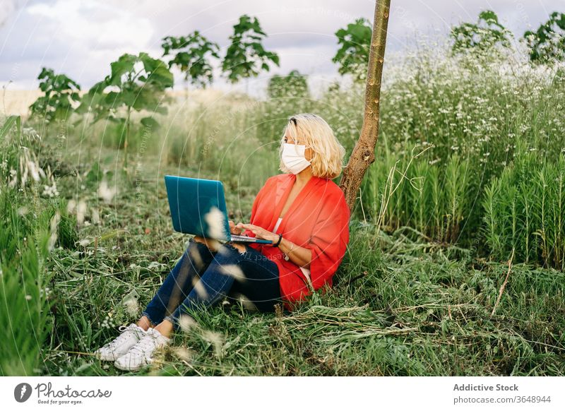 Fokussierte Frau mit Beatmungsgerät arbeitet am Laptop auf einer Wiese benutzend Atemschutzgerät Gras modern Landschaft Natur Coronavirus Windstille Baum