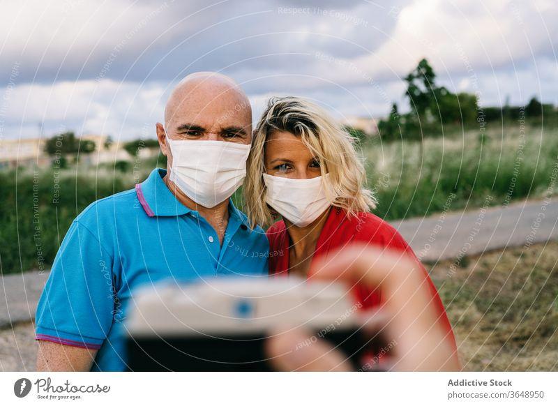 Glückliches Paar mit Atemschutzmasken, das sich am Smartphone selbstständig macht Selfie Mundschutz bezaubernd Coronavirus Sommer Inhalt Handy benutzend Telefon