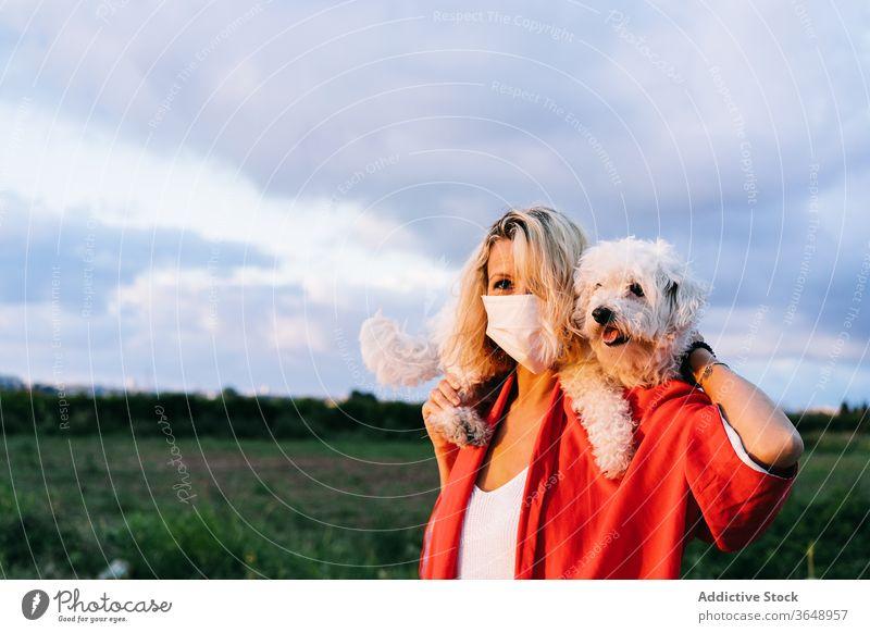 Zufriedene Frau mit Atemschutzmaske und niedlichem kleinen Hund auf den Schultern Bichon frise Atemschutzgerät Landschaft Natur lustig Coronavirus Inhalt lässig