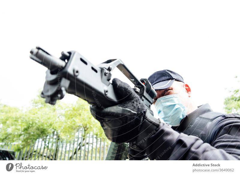Konzentrierter Polizist mit Maschinenpistole während eines Angriffs Mann zielen Operation behüten ernst Schutzmann zerquetschen Sicherheit Gefahr professionell