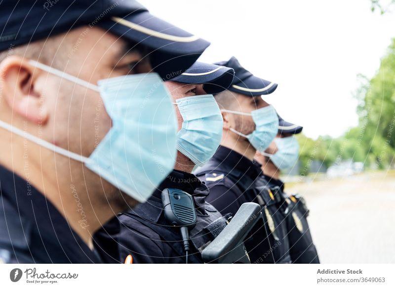 Polizisten mit medizinischen Masken stehen auf der Straße gegen Dienstwagen Männer Patrouille Polizei behüten Kontrolle ernst Sicherheit Arbeit professionell