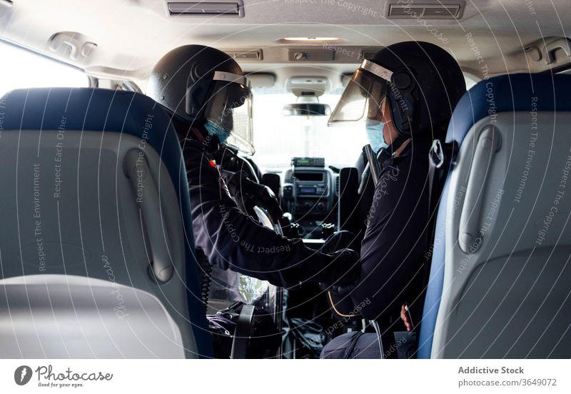 Polizeibeamte im Streifenwagen während des Dienstes Männer Kulisse PKW Gerät Ausrüstung Truppe Sicherheit behüten professionell Uniform Partner medizinisch