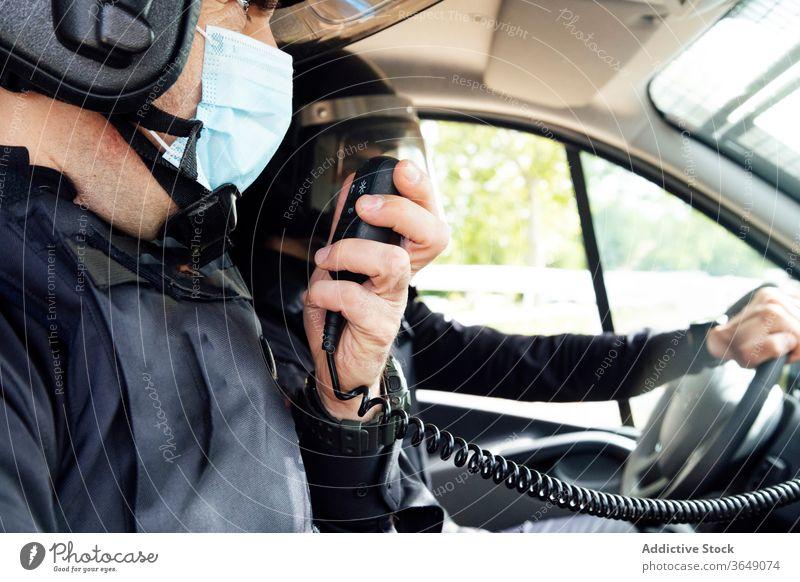 Anonyme Polizisten im Streifenwagen während des Dienstes Männer reden Radio Kulisse Polizei PKW Gerät Ausrüstung Truppe Sicherheit behüten professionell Uniform