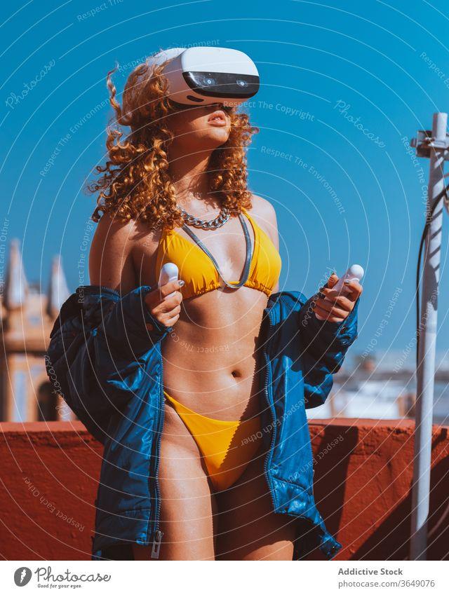 Weibliche Touristin in VR-Headset und Badeanzug schaut sich im Freien Videos an unterhalten Erfahrung Sonnenbad Terrasse Spaß eintauchen benutzend Drahtlos