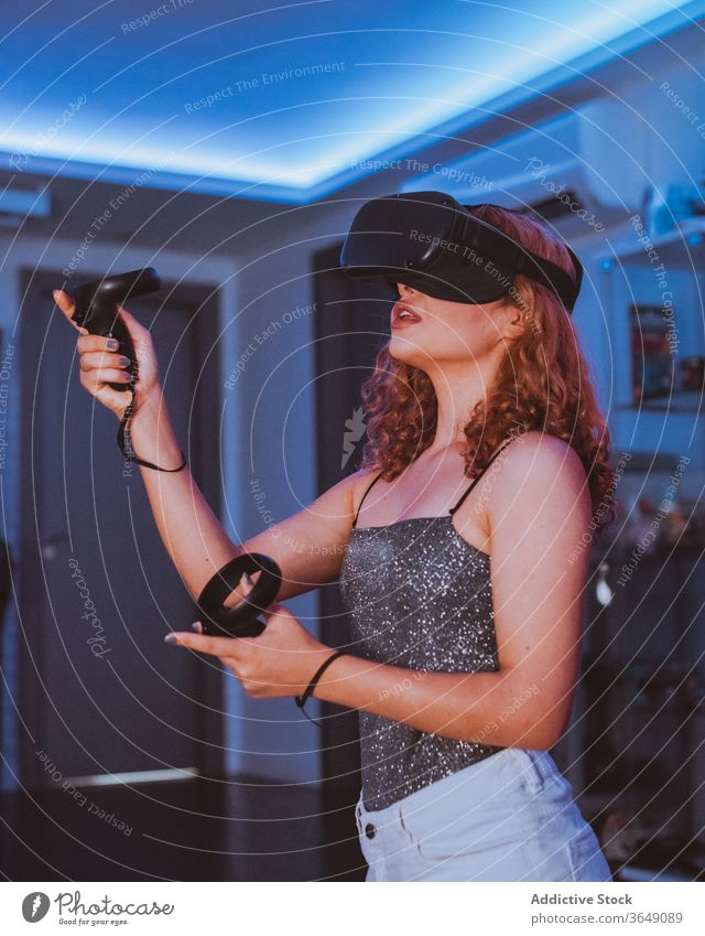 Anonyme Frau spielt zu Hause ein Spiel mit VR-Brille Headset Erfahrung unterhalten Regler Videospiel eintauchen Mund geöffnet neonfarbig benutzend Schutzbrille