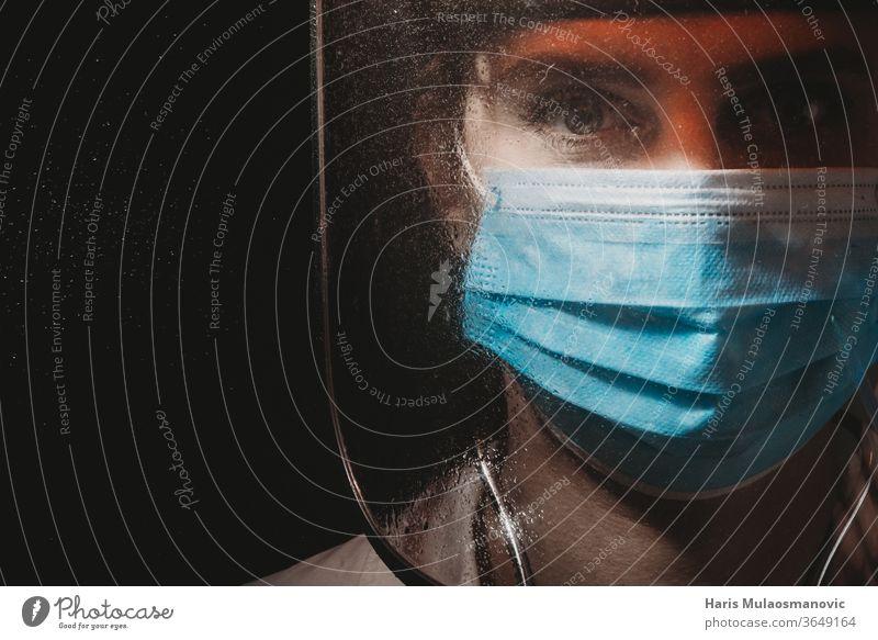 Weibliche Heldenärztin mit Maske und Schild auf schwarzem Hintergrund 2020 Atemschutzmaske schwarzer Hintergrund filmisch Klinik Korona-Epidemie Corona-Virus
