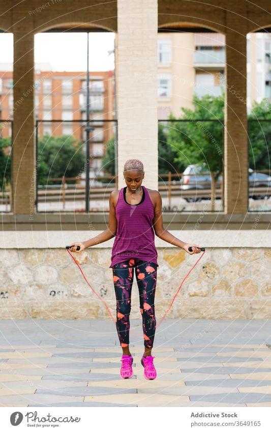 Schwarze Sportlerin springt während des Trainings auf einer Böschung in der Stadt Seil Athlet springen Aufwärmen Übung Sportkleidung Großstadt üben Gesundheit