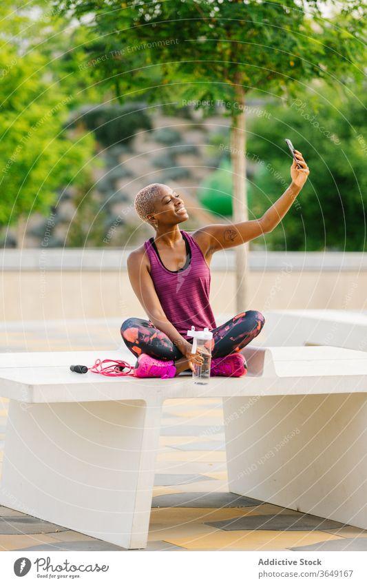 Fröhliche schwarze Sportlerin, die sich nach dem Training am Smartphone selbstständig macht Selfie Pause Sommer Großstadt Sportbekleidung Bank Flasche benutzend