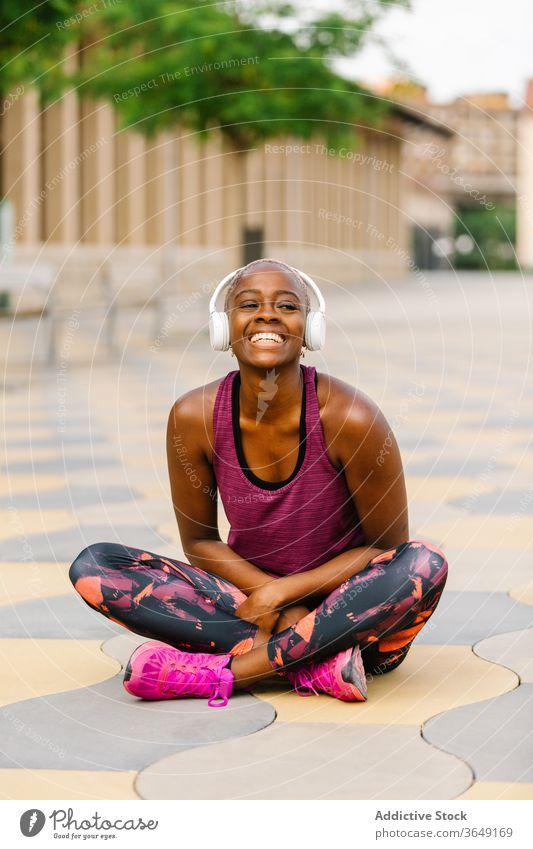 Glückliche schwarze Sportlerin mit Kopfhörer sitzt nach dem Training auf dem Bürgersteig Athlet Headset Sportbekleidung Stauanlage heiter nach vorne lehnen