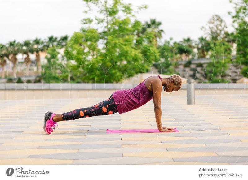 Passgenaue afroamerikanische Frau steht in Ein-Bein-Brett-Pose üben Yoga einbeinige Plankenhaltung Energie Gleichgewicht Ausdauer Konzentration Sportbekleidung