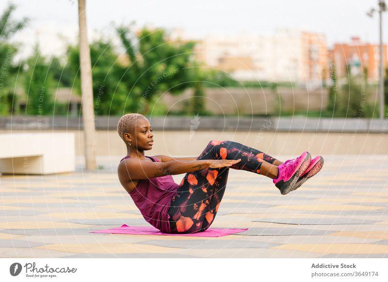 Afroamerikanische Frau sitzt in Half Boat Pose am Damm Halbboot-Pose Yoga üben Gleichgewicht Stauanlage Sportbekleidung Gesundheitswesen Großstadt Handtuch
