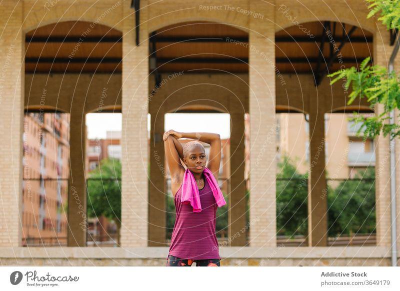 Müde schwarze Sportlerin mit Handtuch steht nach dem Training auf der Böschung Pause Sportkleidung Mund geöffnet müde Gesundheit Gebäude Straßenbelag Großstadt