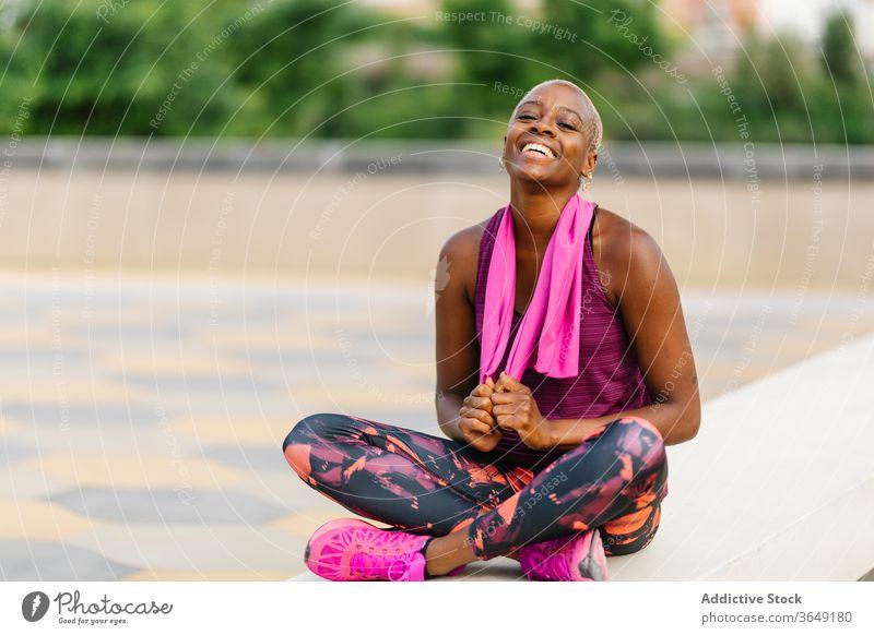 Fröhliche Rückensportlerin mit Handtuch nach dem Training auf der Böschung sitzend Sportlerin Pause Sportkleidung Gesundheit Straßenbelag Großstadt Gebäude