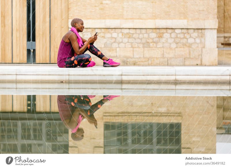 Schwarze Sportlerin surft mit Smartphone im Internet in der Nähe des Stadtbrunnens soziale Netzwerke Pause Springbrunnen Handtuch Reflexion & Spiegelung