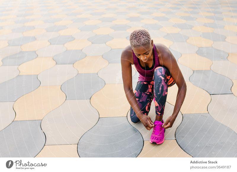 Afroamerikanischer Athlet bindet während des Trainings Schnürsenkel an Turnschuhen Sportlerin Krawatte Schuhbänder Großstadt Kniebeuge Pause Straßenbelag