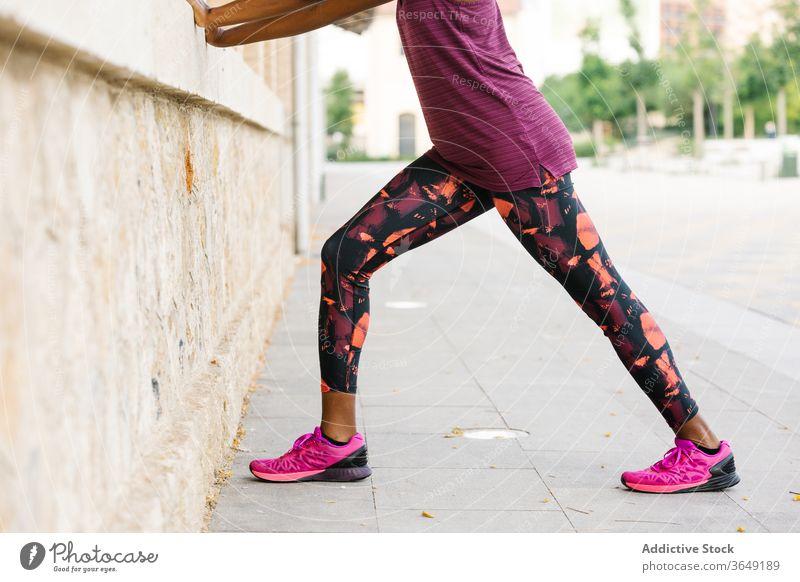 Schwarze Sportlerin, die sich auf dem Bürgersteig in der Nähe eines Backsteinhauses die Beine vertritt Dehnung Übung üben Aktivität Sportbekleidung Gebäude