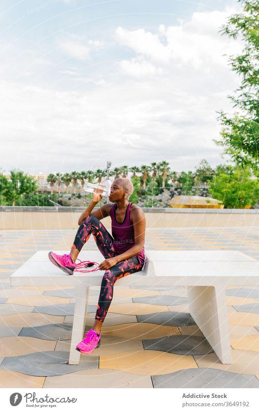 Durstiger schwarzer Sportler trinkt Wasser und surft mit seinem Smartphone im Internet Sportlerin trinken Flasche Pause Bank benutzend Apparatur Gerät Hipster
