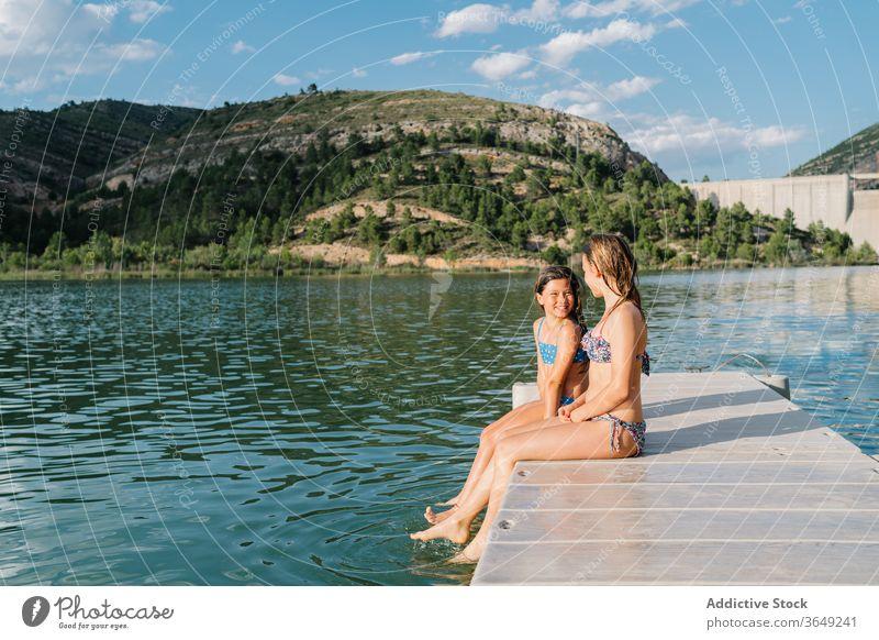 Sorglose Schwestern ruhen sich im Sommer am Pier aus Urlaub Badebekleidung Bikini Mädchen See Kai heiter Zusammensein Kindheit Lächeln Freundschaft