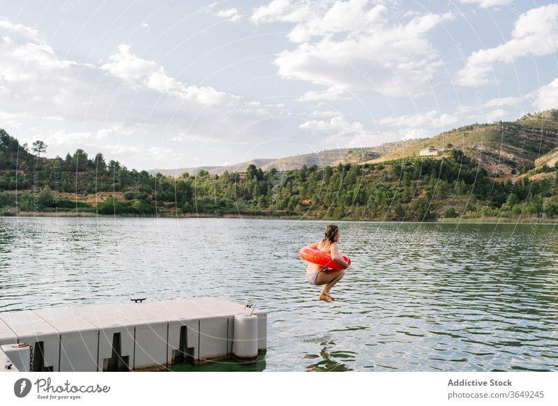 Mädchen springt mit aufblasbarem Ring in den See springen Gummi Teich Bikini Sommer Urlaub Spaß haben Teenager Moment Wasser Glück Erholung sich[Akk] entspannen
