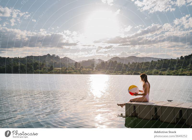 Frau sitzt am Rand einer Mole in der Nähe des Sees Beachball spielen Teich Sommer Badebekleidung Feiertag sitzen Urlaub genießen aufblasbar Gummi Wasser