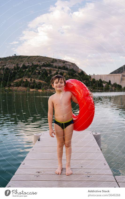 Junge mit aufblasbarem Ring im See Gummi Teich Sommer Urlaub niedlich Lächeln Spaß haben Kind Wasser Glück unschuldig heiter Kindheit sich[Akk] entspannen