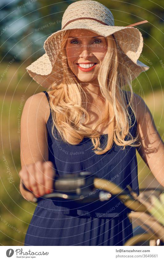Attraktive blonde Frau mit einem freundlichen Lächeln steht mit ihrem Fahrrad in der Frühlingssonne im Freien und trägt einen breitkrempigen Stroh-Sonnenhut