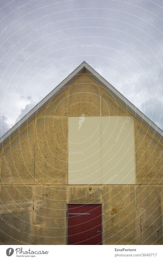 quadratischer Textfreiraum auf der Giebelseite eines alten Hauses mit schmückender roten Tür und lebhaften wolkenbehangenen Himmel Gebäude Fassade Wand Dach
