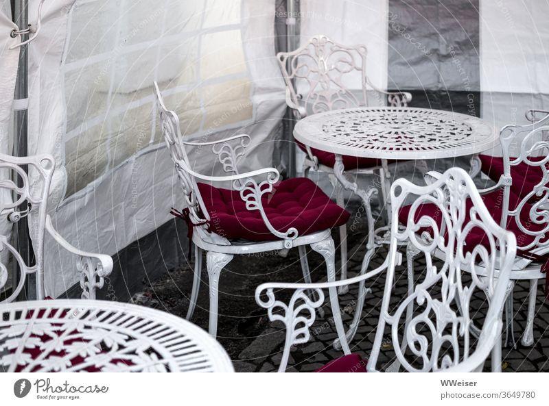 Die Eissaison fällt ins Wasser Eiscafe Stühle Tische Wintergarten Café verregnet kalt Ornament Vintage verziert Gartenmöbel Windschutz Zelt überdacht leer