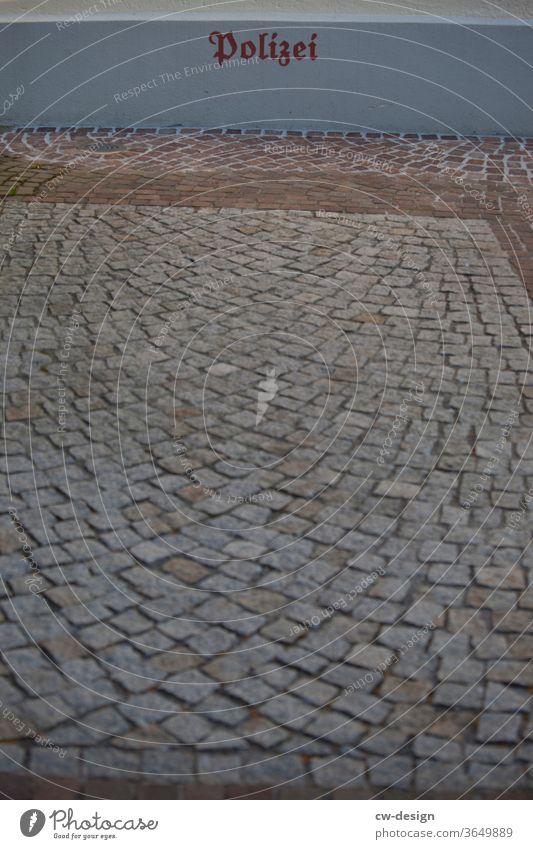 gepflasterter Parkplatz der Polizei Schriftzeichen Farbfoto Zeichen Menschenleer Detailaufnahme Außenaufnahme Textfreiraum unten Textfreiraum links