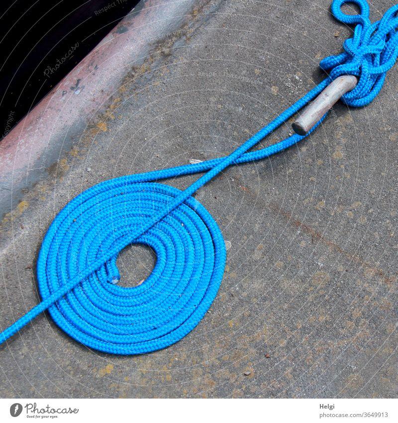etwas Ordnung muss sein - blaues Befestigungsseil liegt ordentlich aufgerollt und unordentlich um einen Stab gewickelt an einer Kaimauer Seil Tau umwickelt