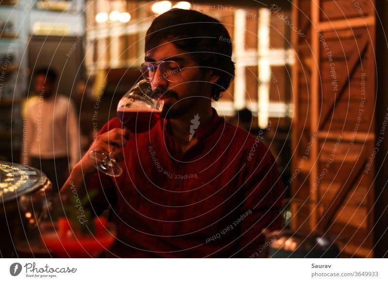 Junger Mann mit rotem Hemd, während er Rotwein aus einem Kelch trinkt, in einer Bar mit bunten Lichtern um ihn herum. Lifestyle trinken im Innenbereich Feier