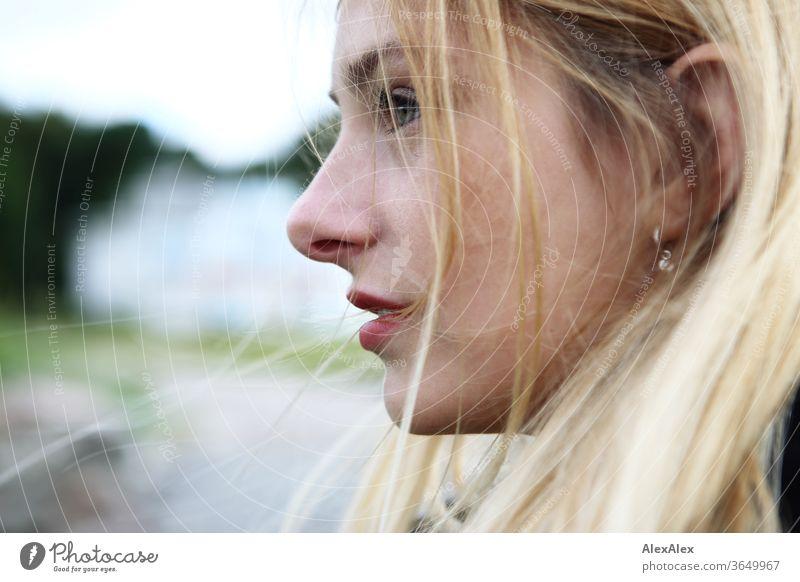 Seitliches Portrait einer jungen, blonden Frau junge Frau schön schlank seitlich langhaarig windig rote Lippen ästhetisch Sommer Ausflug Schönes Wetter Model