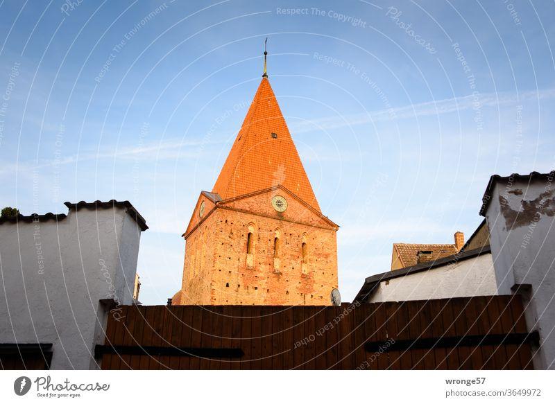 Kirchturm der Schwaaner St. Paulus Kirche hinter einem Hoftor Ortsmitte Außenaufnahme Farbfoto Menschenleer Architektur Religion & Glaube Sehenswürdigkeit