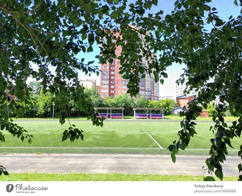 Leeres grünes Fußballfeld in der Nähe einer Schule und des Wohnhauses in Russland. Stadion und Fußballfeld mit leeren Zuschauerplätzen. Fit halten und sich im Freien bewegen. Stadtansicht in einem Rahmen aus Blättern.