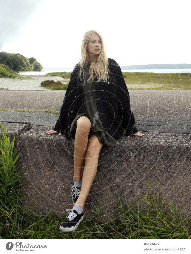 Gegenlicht Portrait einer jungen, blonden Frau auf einem Betonblock am Meer junge Frau schön schlank langhaarig windig ästhetisch Sommer Ausflug Schönes Wetter