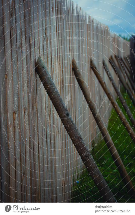Intelligente Lösung - einfach  gut und   billig. Holzstangen stehen als Stütze an einem Bretterzaun. bretterwand Außenaufnahme Farbfoto Menschenleer Natur Tag