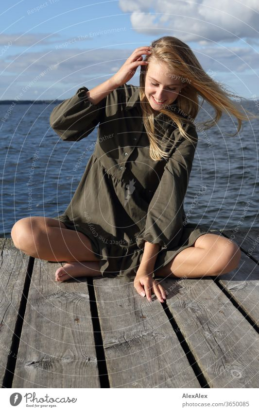 Ganzkörper- Portrait einer jungen, blonden, barfüßigen Frau auf Holzsteg im Meer junge Frau schön schlank langhaarig windig ästhetisch Sommer Ausflug