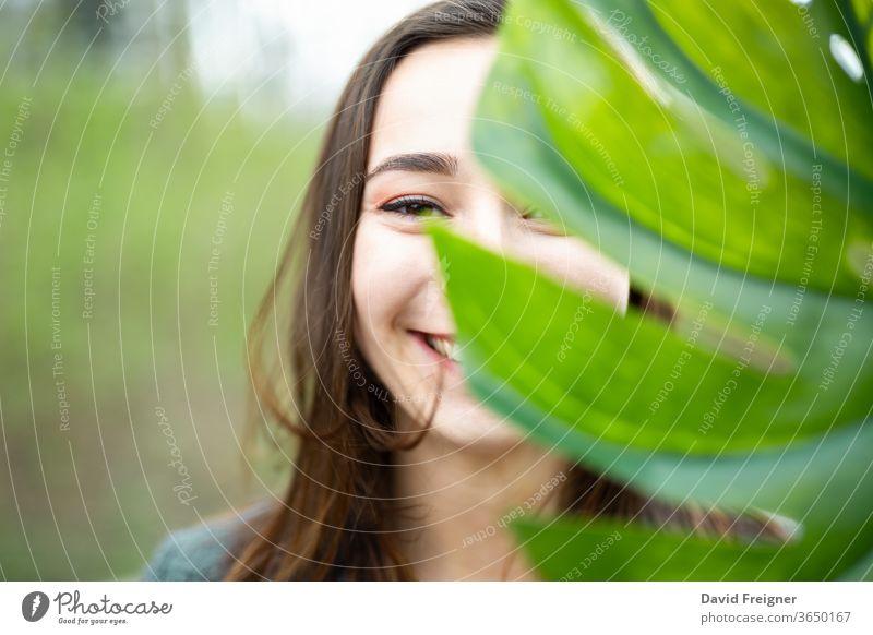 Schöne natürliche junge Frau in Nahaufnahme hinter einem großen Monsterblatt mit grünem Hintergrund in den Wäldern. Lächeln Gesicht Blatt attraktiv Sauberkeit
