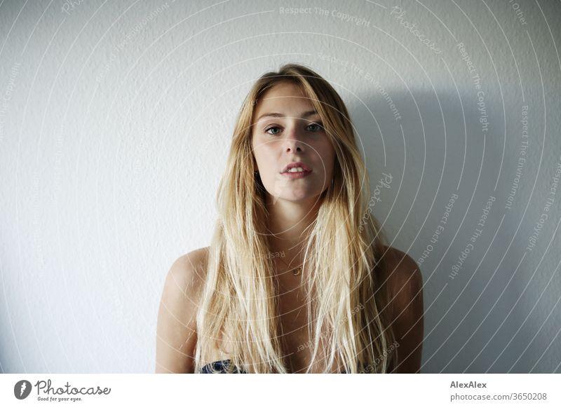 Portrait einer schönen, jungen, blonden Frau vor einer weißen Wand junge Frau schlank langhaarig ästhetisch Model Identität sportlich Zentralperspektive