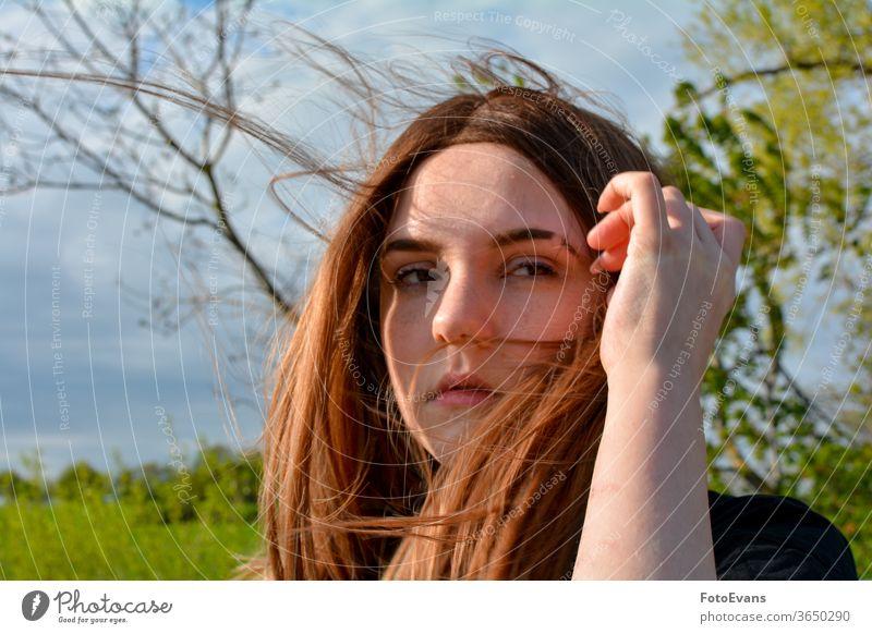 Mädchen steht mit wehendem Haar in der Natur, Hand auf dem Kopf Arme Wind Porträt Mode Tag Schönheit modern attraktiv Baum im Freien Sonnenlicht echte Person