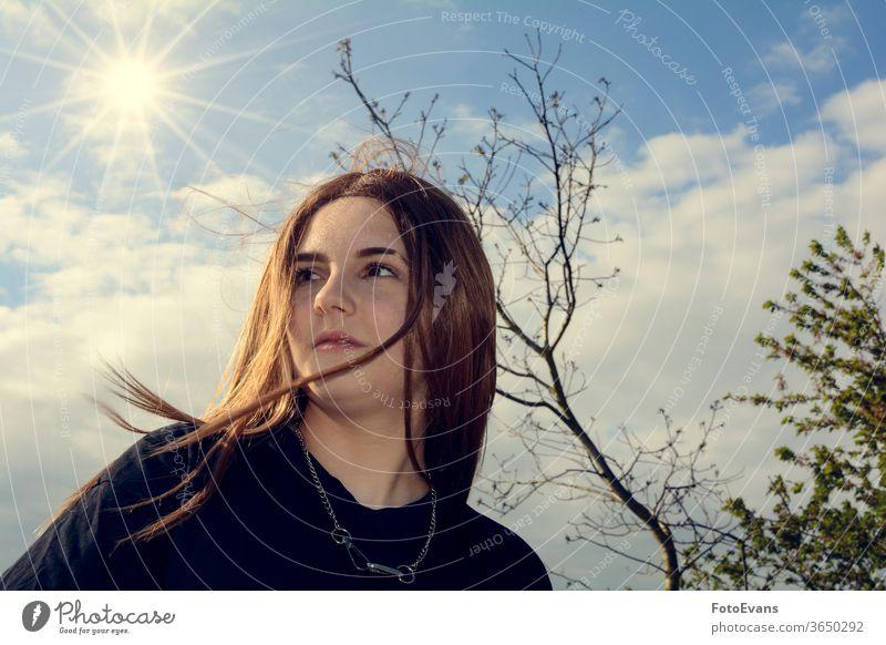 Mädchen steht im Freien mit blauem Himmel, Baum und Sonne Porträt Natur Person Tag Schönheit modern attraktiv wirklich echte Person Behaarung Textfreiraum