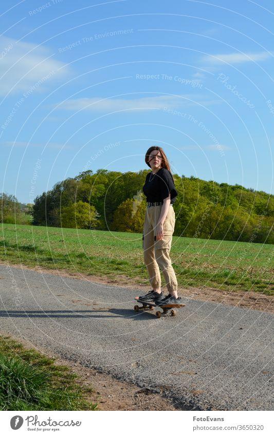 Junge Frau läuft Schlittschuh auf einer Straße in der Natur Porträt sportlich genießend Mode Tag Schönheit Schlittschuhlaufen Hand modern attraktiv Mädchen