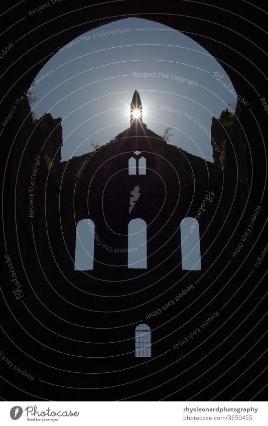 Die Sonne flackert durch eine Öffnung in der Spitze einer Mauerruine einer alten Kathedrale. Sommertag mit strahlend blauem Himmel, Religion Glaube Wunsch Gebet