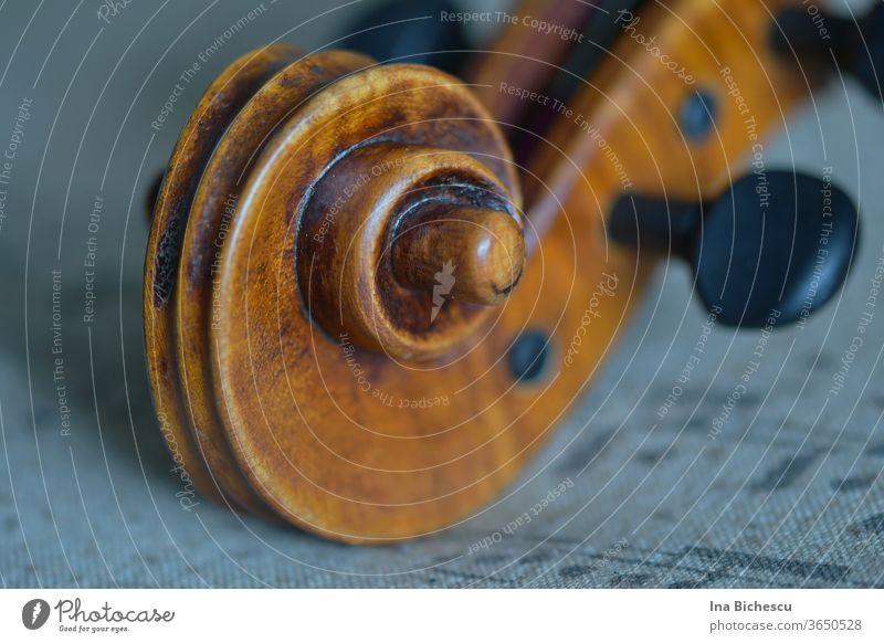 Der Kopf einer Geige aus Holz mit der Schnecke und ein schwarzen Stimmwirbel auf einem grauen Stofftuch mit Musik Noten Druck. violine viola bratsche kopf