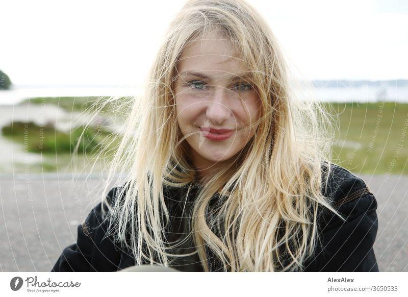 Gegenlicht Portrait einer jungen, blonden, lächelnden Frau am Meer junge Frau schön schlank langhaarig windig ästhetisch Sommer Ausflug Schönes Wetter Model