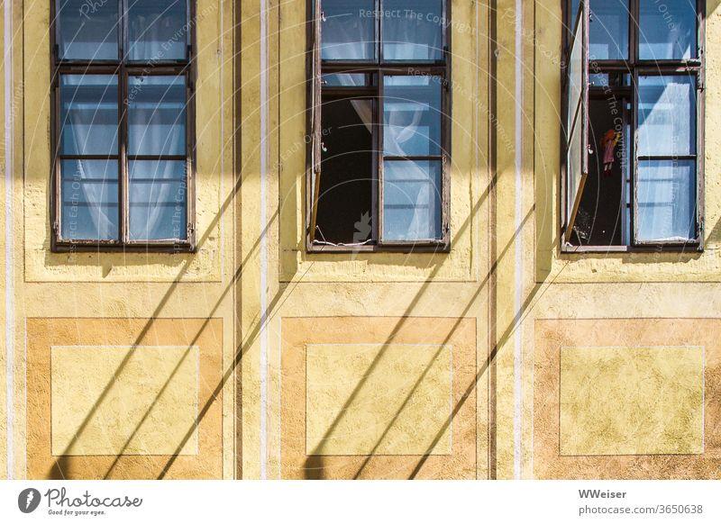 Schräge Schatten auf einer alten Fassade Fenster offen Diagonale Gardinen Vorhänge dunkel Zimmer Einblick Haus gelb historisch Wand Gebäude Licht Sonne Puppe