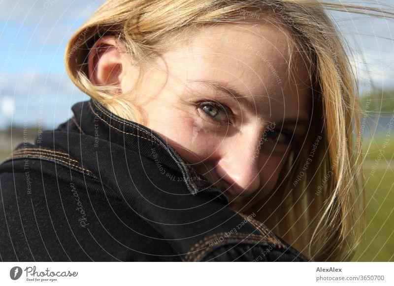 Seitliches Portrait einer jungen, blonden, lächelnden Frau junge Frau schön schlank seitlich langhaarig windig ästhetisch Sommer Ausflug Schönes Wetter Model