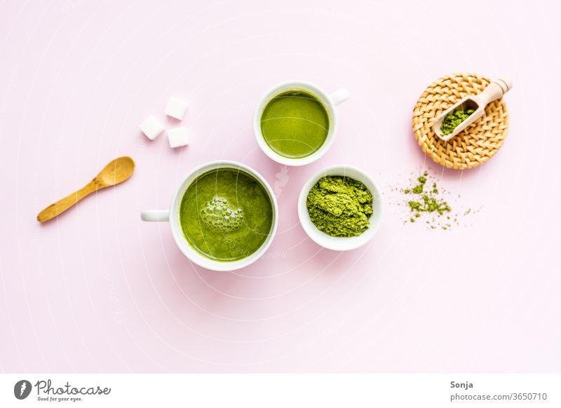 Matcha Latte in zwei weißen Tassen und Pulver in einer Schüssel auf einem rosa Hintergrund. Flat lay, Zutaten. grün Tee Getränk Matcha-Tee trinken Rührbesen