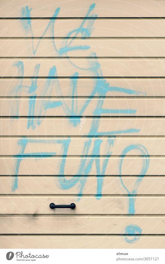 """""""WE HAVE FUN"""" steht in großer hellblauer Graffiti - Druckschrift auf einem beigefarbenen Metall-Garagentor über dem Griff we have fun Schmiererei"""